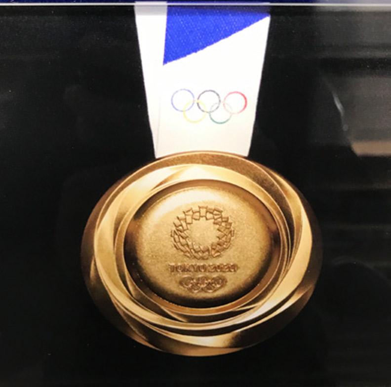由川西純市設計的2020 年東京奧運金牌,獎牌呈立體旋渦狀,中間刻上東京奧運會「組市松紋」集合而成的會徽。(攝自日本奧林匹克博物館)