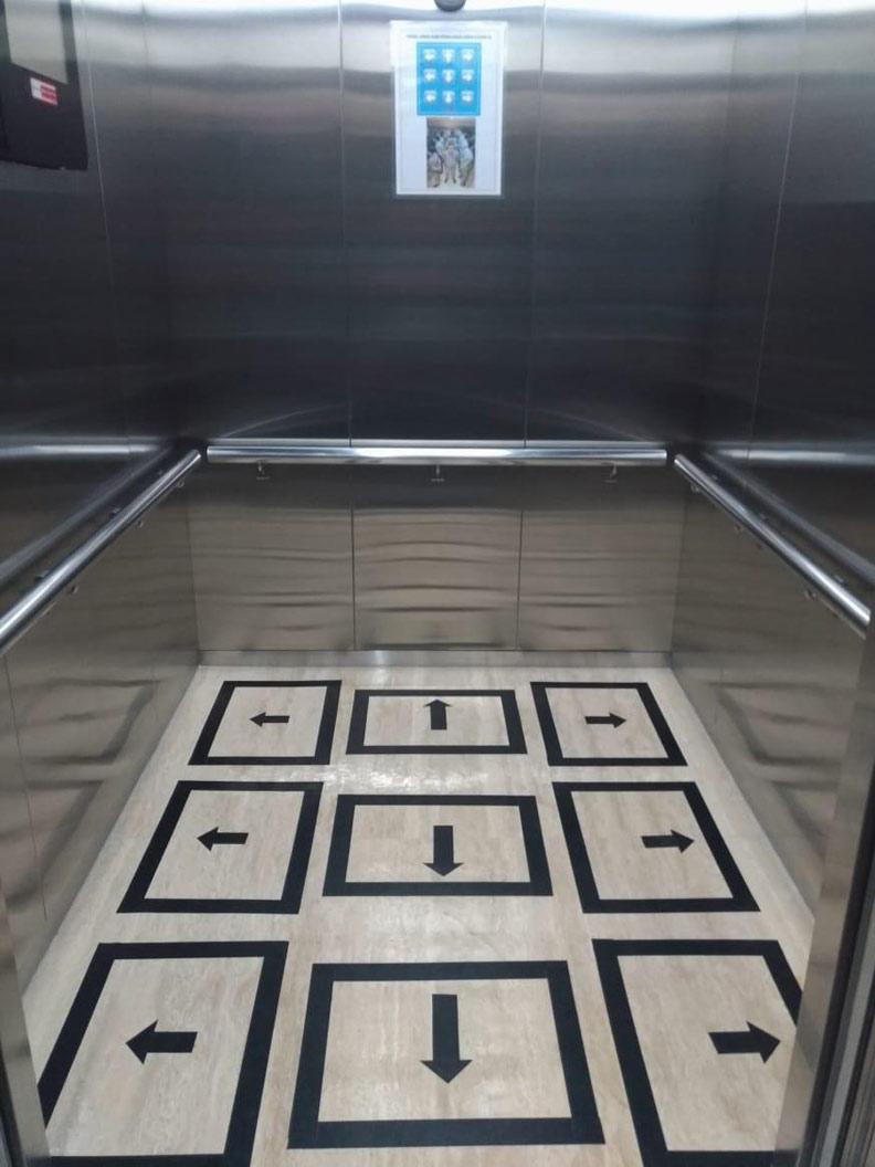 印尼辦公大樓電梯內的地板,被畫上防疫分隔區。作者提供