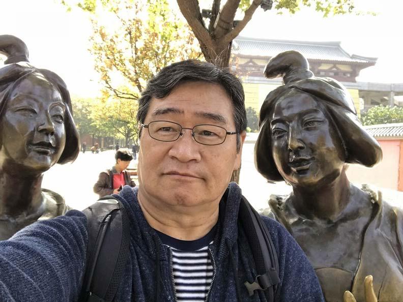 在西安大雁塔寺外,與2位大唐宮女們自拍的王浩一。