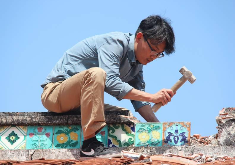 搶救屏東馮安德家族「麒洛德源堂」花磚時,徐嘉彬親自爬上屋頂,小心卸除花磚。徐嘉彬提供。