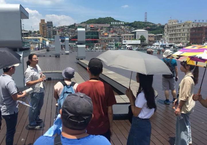 「見書店」老闆陳顥樺(左二)在基隆港邊向遊客導覽台灣的海洋文化。圖片取自見書店