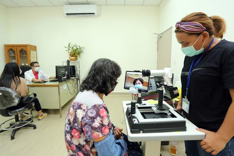 病患坐在5G連網的眼底鏡前,護理人員操作儀器桿,將視網模的影像,「直播」給遠方的醫師。