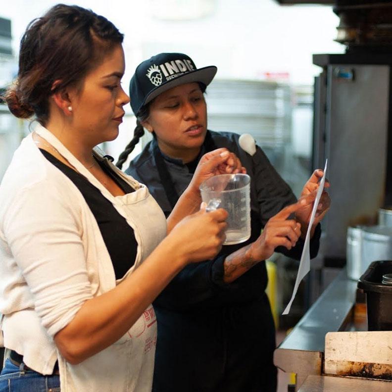 Food Shift 廚藝訓練導師 Suzy Medios(右)教導學徒用手頭容易取得的食物準備健康的餐點。來源:Food Shift Instagram