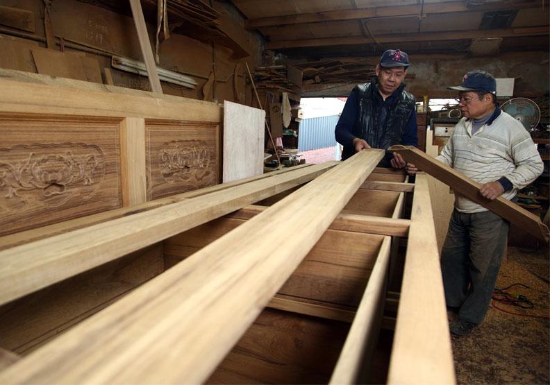 協大木器行旁的工廠中,兩位工匠正在製作神桌。陳之俊攝。