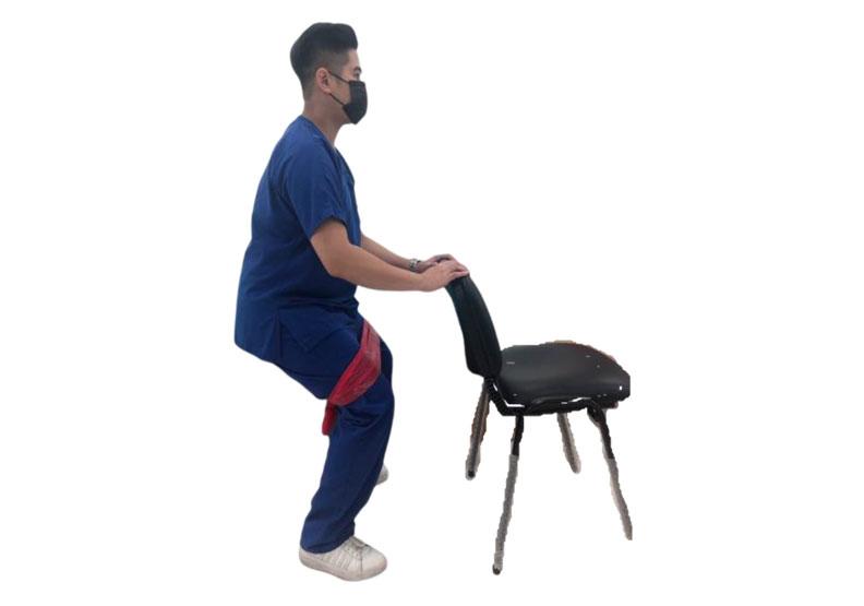 利用彈力帶及椅子輔助進行半蹲訓練。台灣運動醫學學會提供